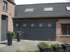porte de garage gris avec hublot par Yves Carton à Lille